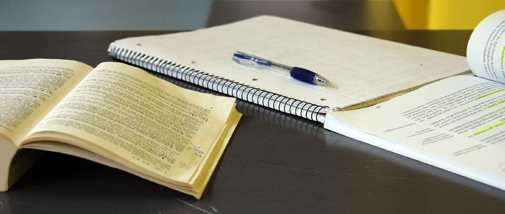 Book, notebook, and pen lying on a table