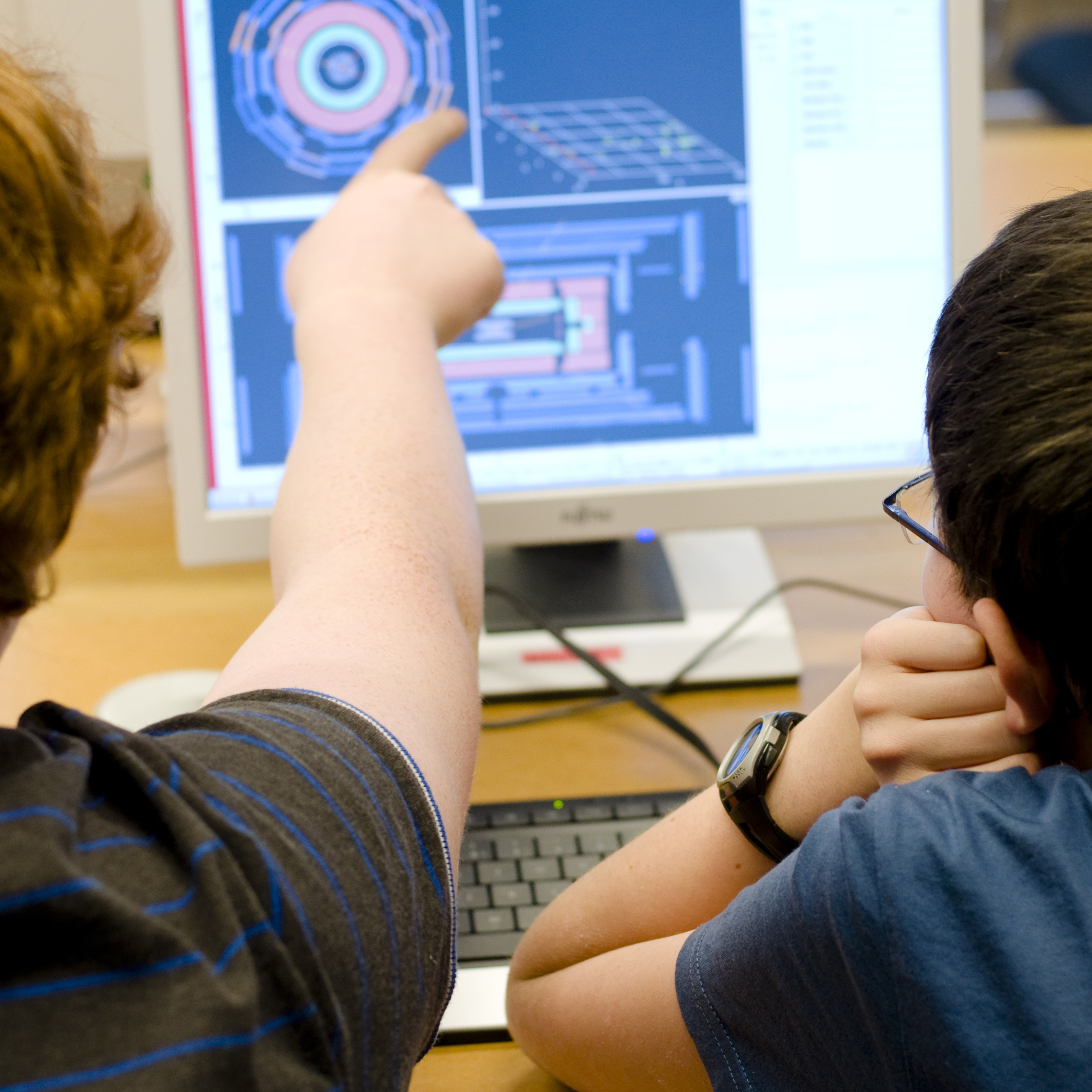 Two school students sitting in front of a monitor