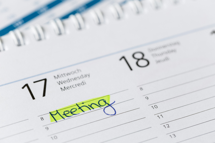 "The word ""Meeting"" written on a calendar"